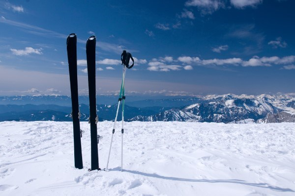 skis in snow with mountains in the background