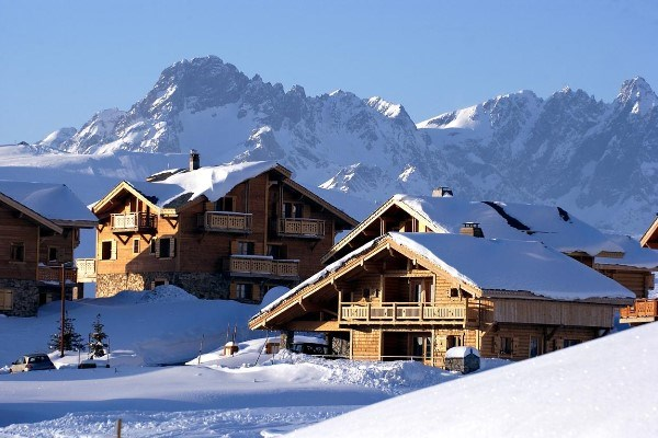 sunny photo of snow covered chalets in Alpe d'huez with mountains in the background