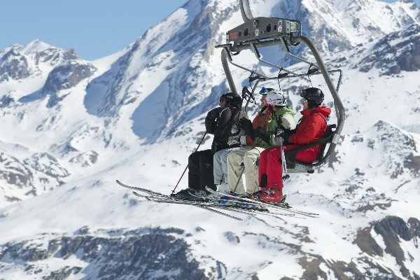 skiers on a chairlift with a snow covered mountain in the background