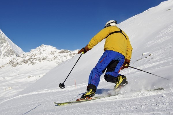 man doing telemark skiing with mountains in background