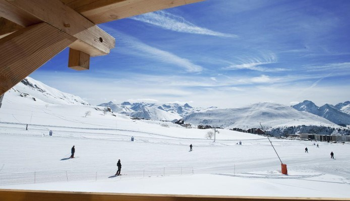 people skiing down a piste beneath vip ski village chalets in alpe d'huez