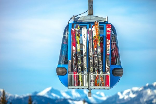 skis on side of a cable car with mountains in background